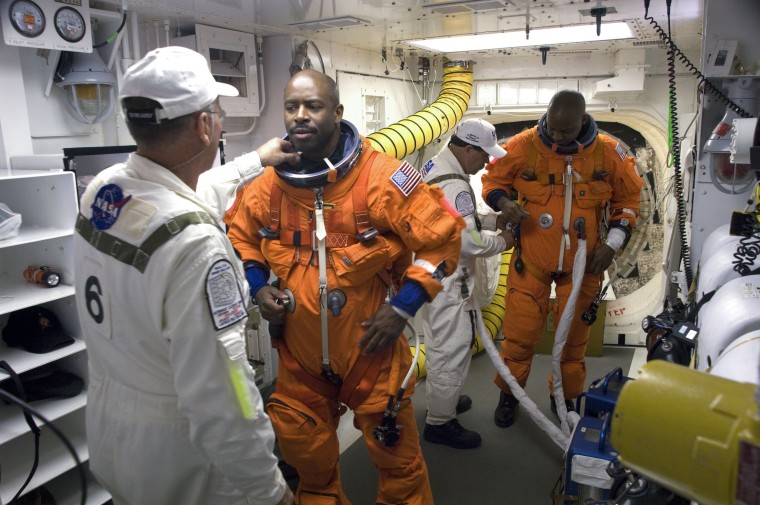 At Launch Pad 39A at NASA's Kennedy Space Center in Florida, suit technicians ensure the proper fit of the launch-and-entry suits of the STS-129 crew members. Mission Specialists Leland Melvin and Robert L. Satcher Jr., at right, prepare to enter space shuttle Atlantis.