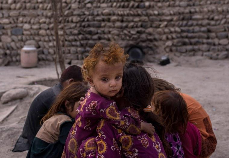 Image: A young Afghani girl hugs her sister