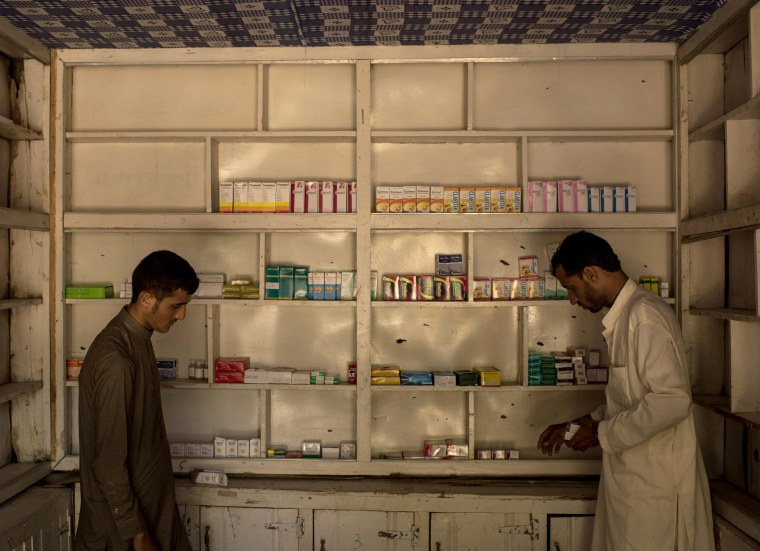 Image: Men restock a pharmacy