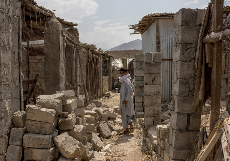 Image: A boy walks through buildings damaged from fighting