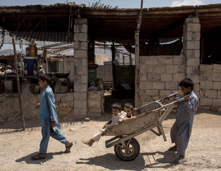 Image: Children play with a wheel barrow