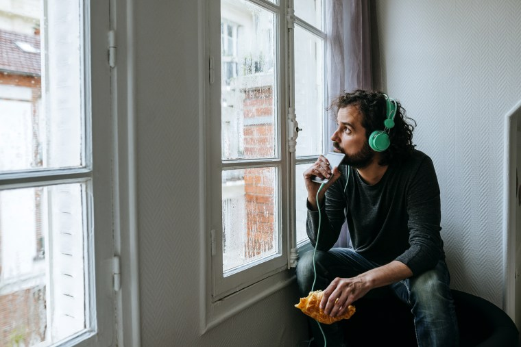 Image: Man Listening to Music with Headphones and Smartphone at Home