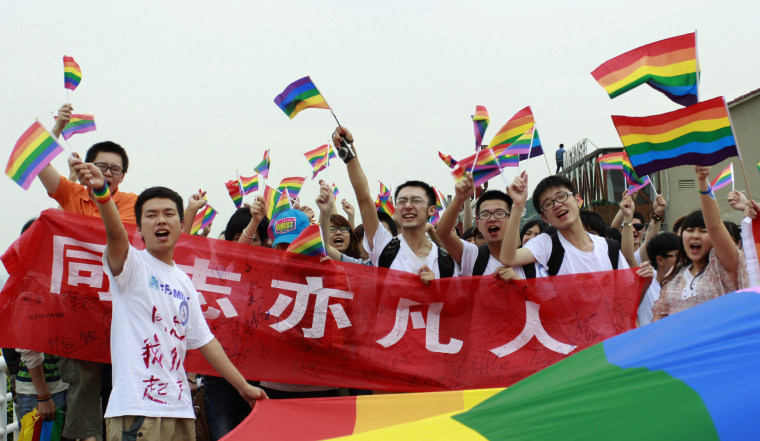 Image: Youngsters hold rainbow flags during their anti-discrimination parade in Changsha.