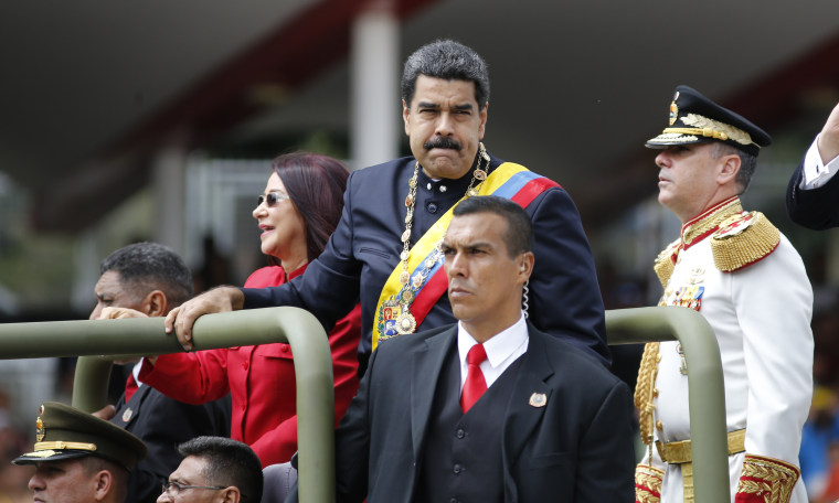 Venezuela's President Nicolas Maduro and first lady Cilia Flores ride in a vehicle during a military parade commemorating the country's Independence Day in Caracas, Venezuela, Wednesday, July 5, 2017.