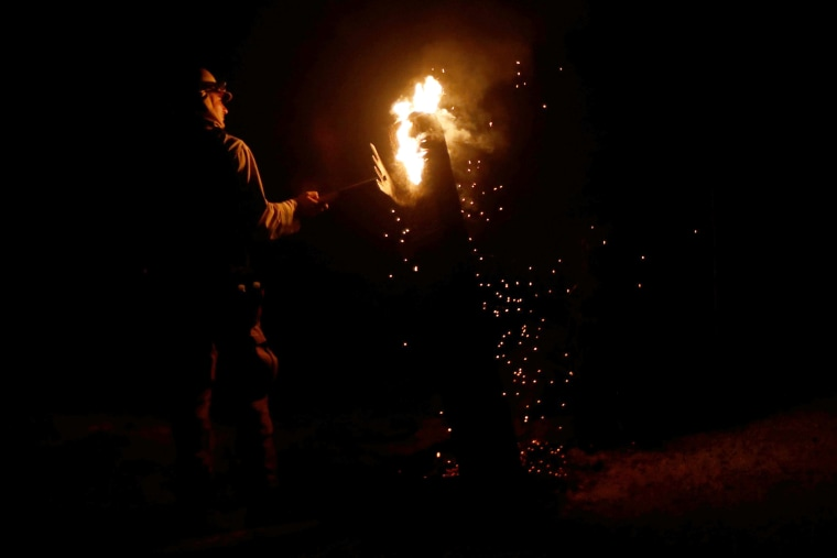 Image: A firefighter works on dousing a burning pole on July 18.