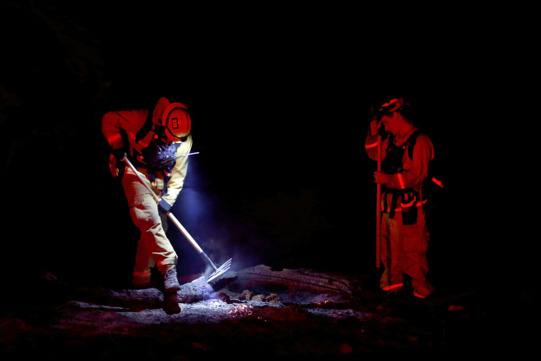 Image: Two firefighters work on a hot spot on July 19.