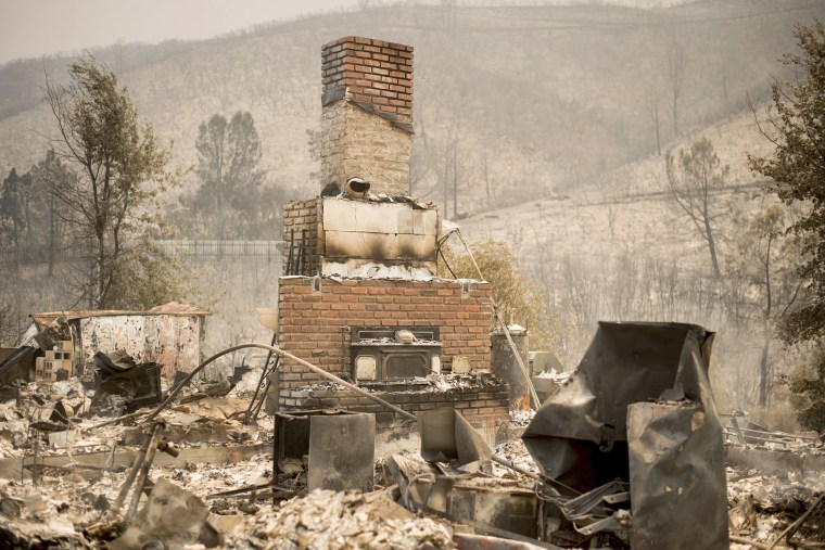 Image: A chimney stands at a burned residence on Yaqui Gulch Road on July 19.