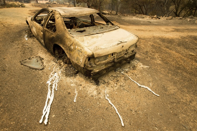 Image: A scorched car rests next to a residence leveled by the Detwiler fire on July 19.