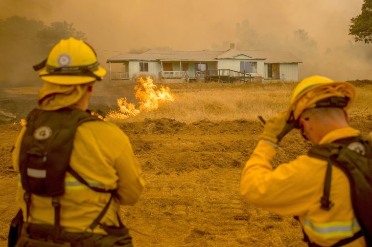 Image: Firefighters watch as flames surround a home in Mariposa on July 19.