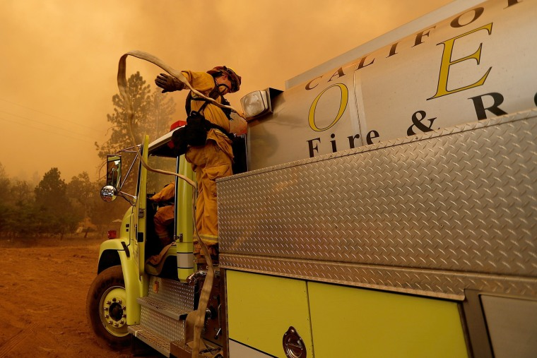 Image: A firefighter pulls a water hose from an engine as he prepares to defend a structure from the fire on July 19.