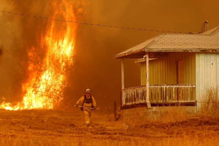 Image: A firefighter walks near a home as flames from the fast-moving Detwiler fire approach on July 19.