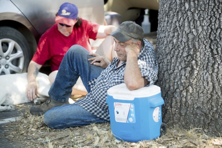 Image: Evacuees Don and Jodi Roark, who are unsure if their Bear Valley house is still standing, rest outside a Red Cross center for Detwiler fire evacuees in Oakhurst, California, on July 19.