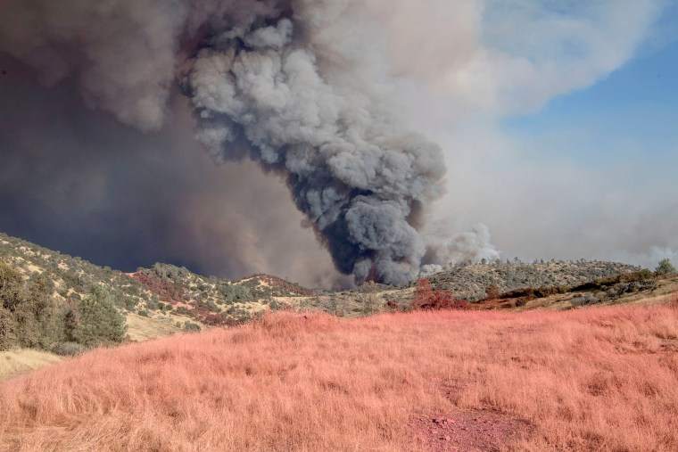 Image: With pink retardant in the foreground, fire blows up on the north side of the Merced River after authorities ordered evacuations on July 18.