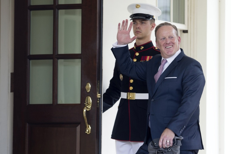 Image: Outgoing White House Press Secretary Sean Spicer waves beside a U.S. Marine as he enters the West Wing of the White House in Washington, DC, July 21, 2017.