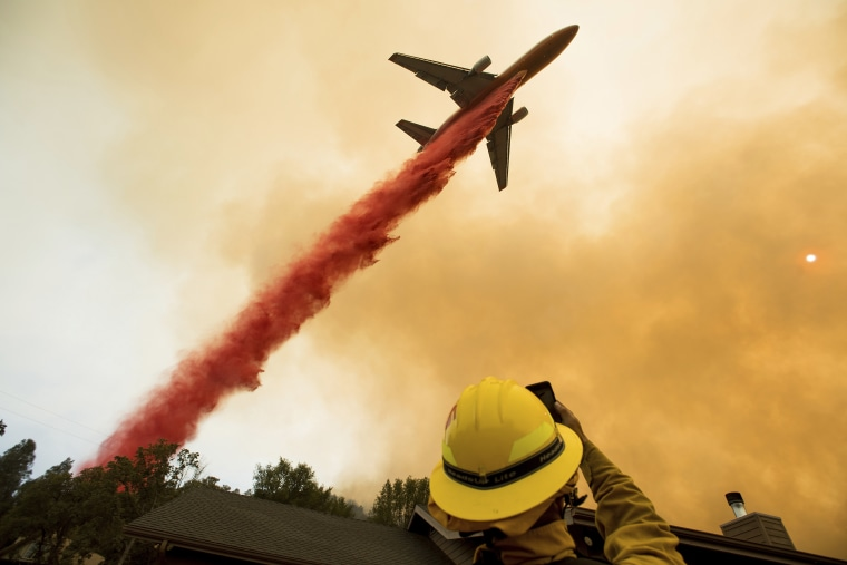 An air tanker drops retardant while battling a wildfire near Mariposa, Calif., Wednesday, July 19, 2017.
