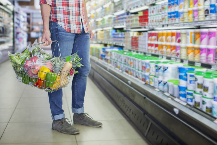 Image: A man carries a shopping basket in a grocery store