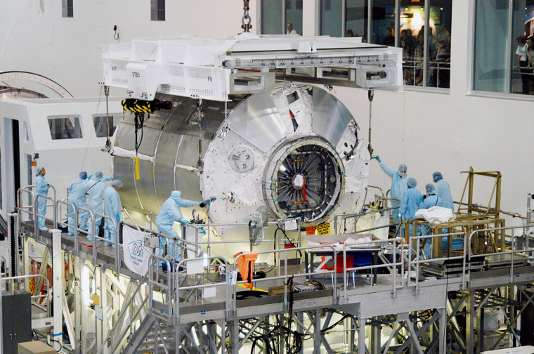 In the Space Station Processing Facility at NASA's Kennedy Space Center, workers help the Multi-Purpose Logistics Module Donatello settle onto a work stand in February 2004.