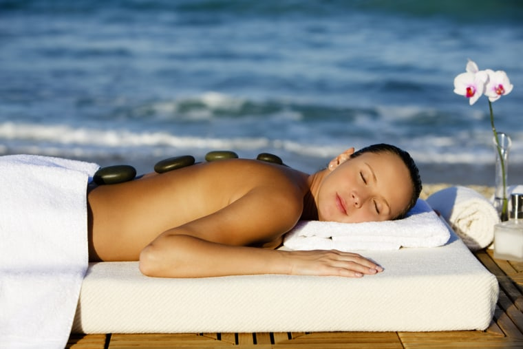 Image: Woman gets a hot stone spa massage at the beach