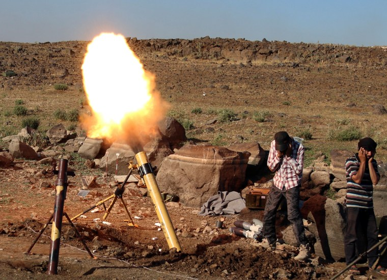 Image: Rebel fighters fire mortar shells towards forces loyal to Syria's President Bashar al-Assad in Quneitra province, bordering the Israeli-occupied Golan Heights
