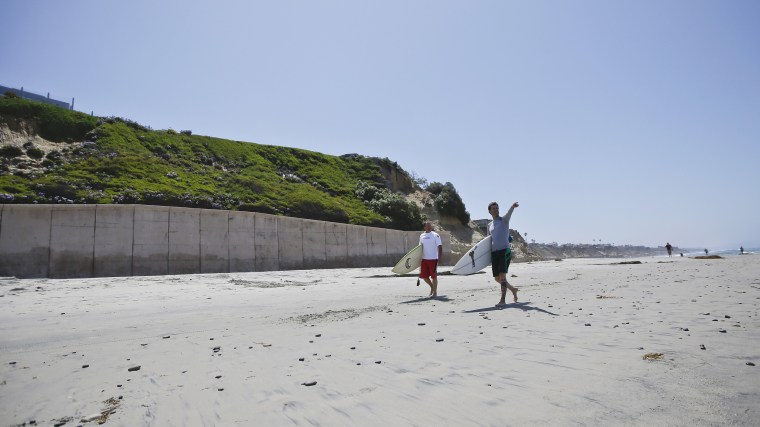 Surfers walk the sand in Solana Beach, Calif., in 2013, below a seawall which holds back the ocean and supports the hill side where homes sit precariously perched atop cliffs.