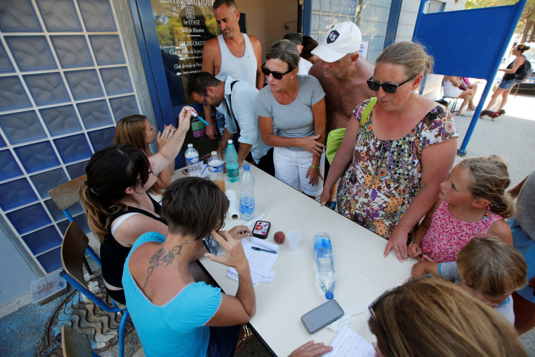 Image: Employees at a gymnasium speak to tourists who were evacuated due to a forest fire in Bormes-les-Mimosas