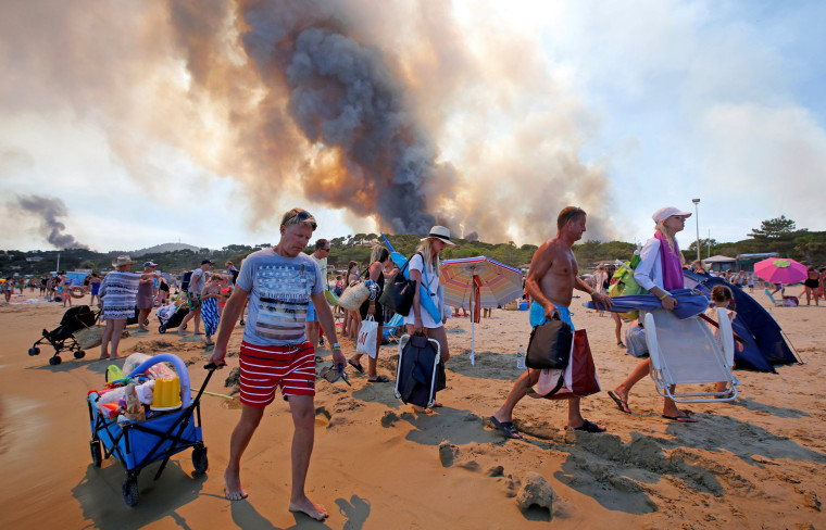 Image: Tourists evacuate the beach as smoke fills the sky above a burning hillside in Bormes-les-Mimosas