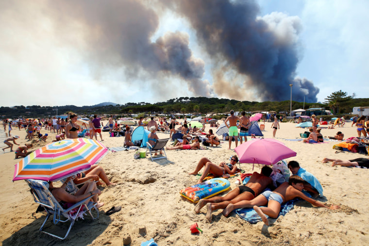 Image: Tourists stand on the beach and watch as smoke fills the sky above a burning hillside in Bormes-les-Mimosas