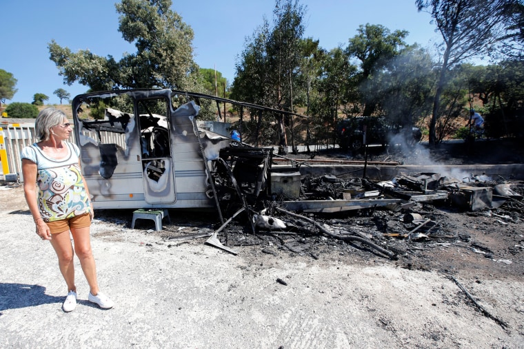 Image: A woman reacts near charred debris of vehicles that were destroyed by fire in a parking lot for camping cars in Bormes-les-Mimosas