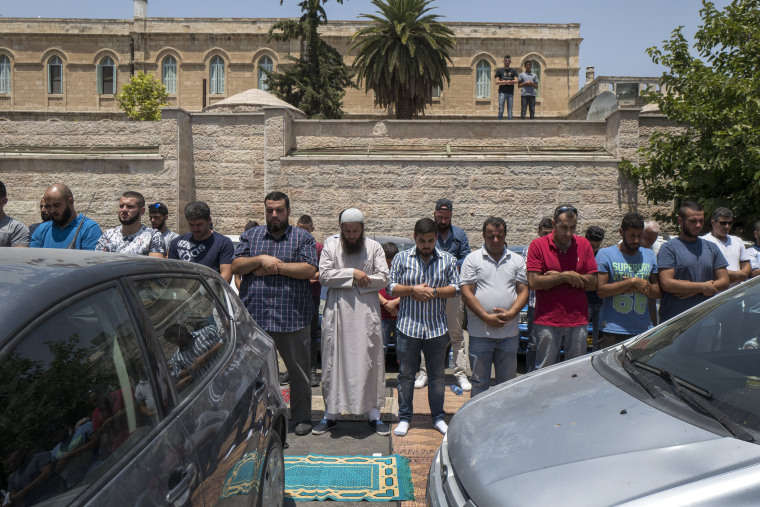 Image: Palestinian Muslims hold prayers in a parking lot