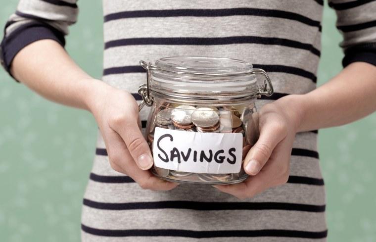 Image: 10 year old holding savings in jar