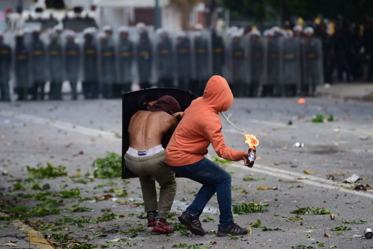 Image: An anti-government activist prepares to throw a Molotov cocktail at members of the National Guard