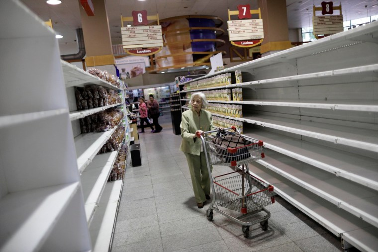 Image: People buy food and other staple goods inside a supermarket in Caracas