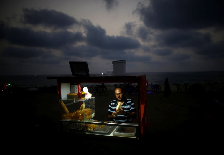 Image: A Palestinian vendor sells snacks on a beach during a power cut