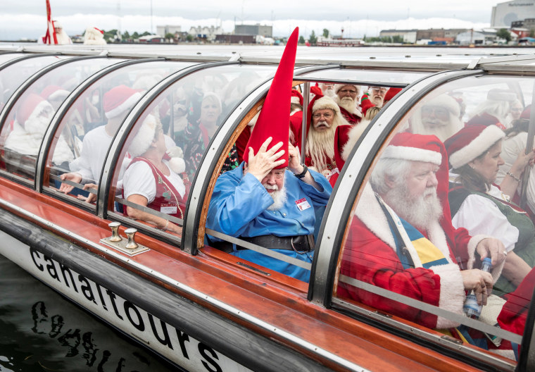 Image: People dressed as Santa Claus take a canal tour of Copenhagen