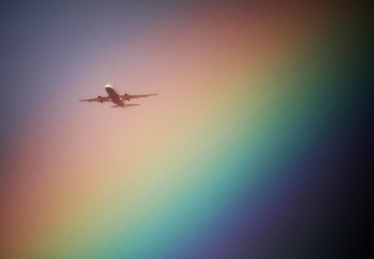 Image: An aeroplane flys near a rainbow on its way to Heathrow Airport in London