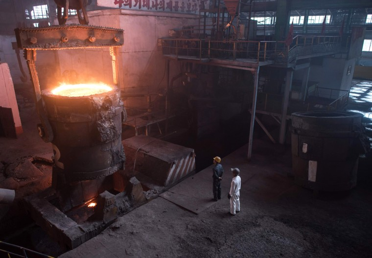 Image: Workers watch as molten steel is transferred from a furnace during production at the Chollima Steel Complex