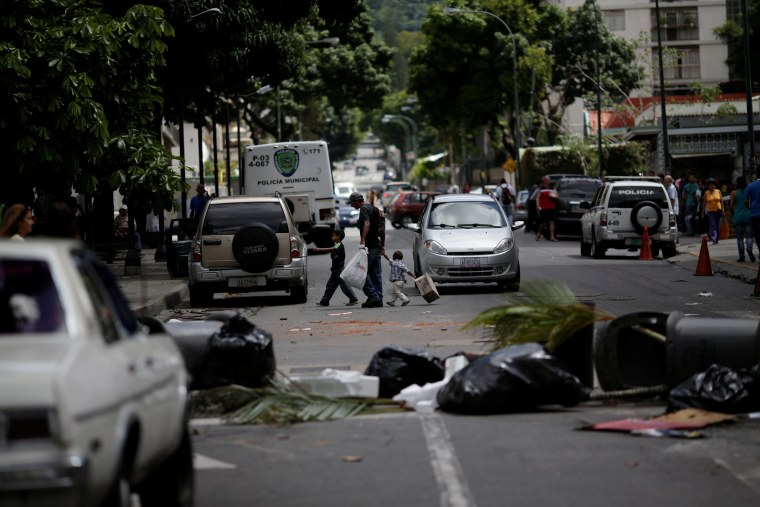 Image: People walk through a barricade after a strike called to protest against Venezuelan President Nicolas Maduro's government in Caracas