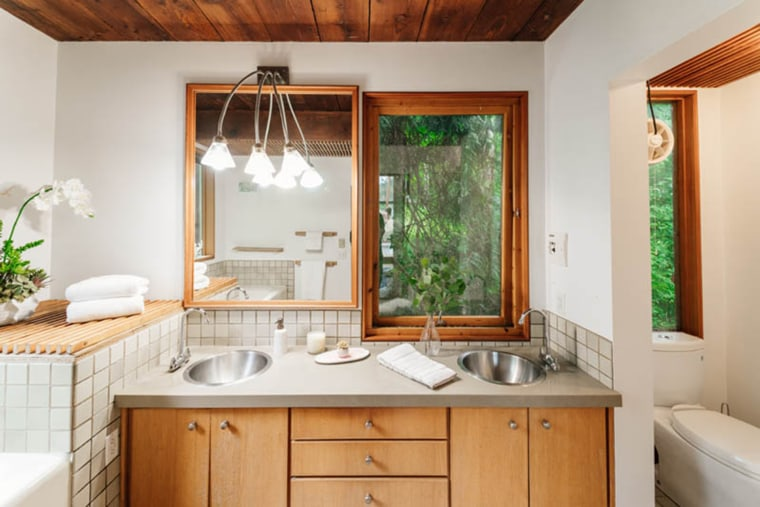 "The bathroom layout offers new meaning to the saying, ""find yourself in nature.""  The designer placed a window directly next to the vanity-style mirror."