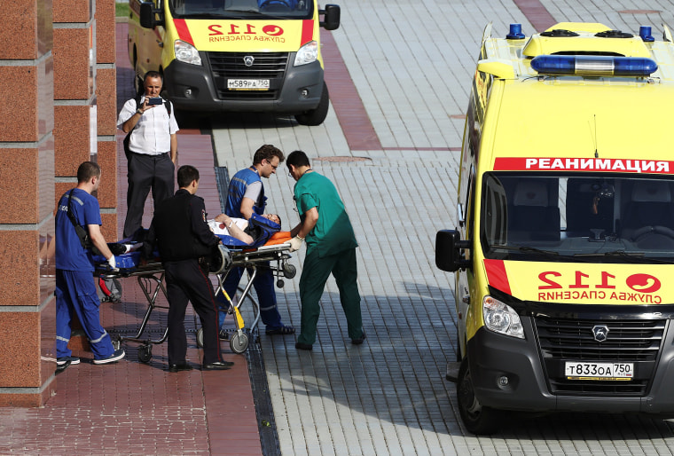 Image: Medics transfer an injured man outside the Moscow regional court building
