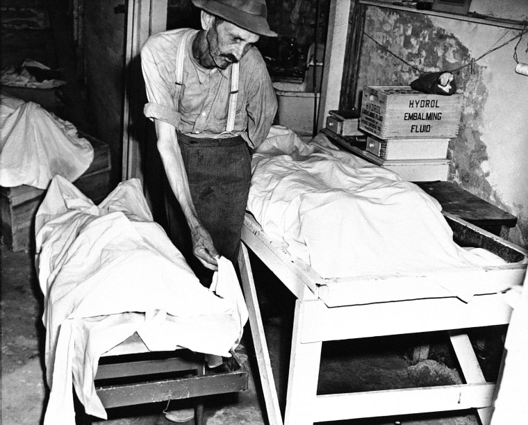 A coroner places a sheet over the body of one of the victims of the Moore's Ford lynching on July 27, 1946.