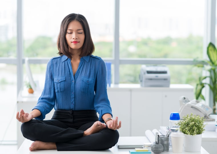 Image: A businesswoman meditates and practices yoga in her office