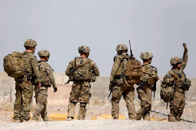 Image: U.S. troops walk outside their base in Uruzgan province