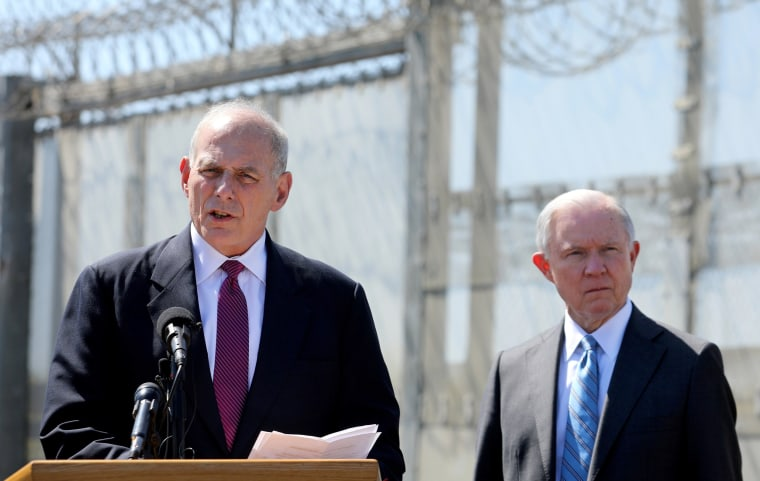 Image: Secretary of Homeland Security John Kelly speaks as Attorney General Jeff Sessions listens as they brief the media during a visit to the U.S. - Mexico border fence in San Diego