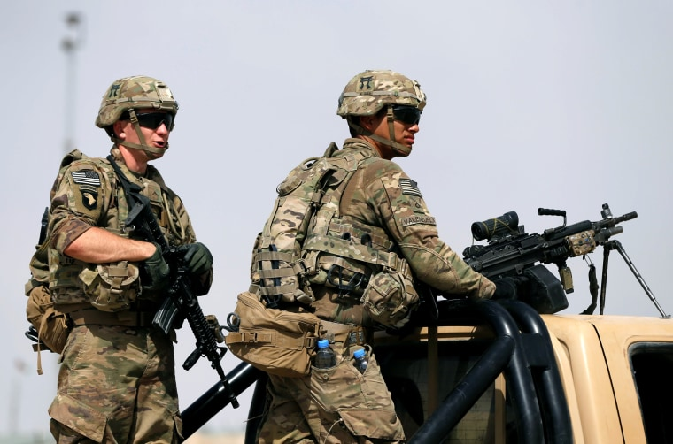 Image: U.S. troops keep watch on the back of a truck outside their base in Uruzgan province