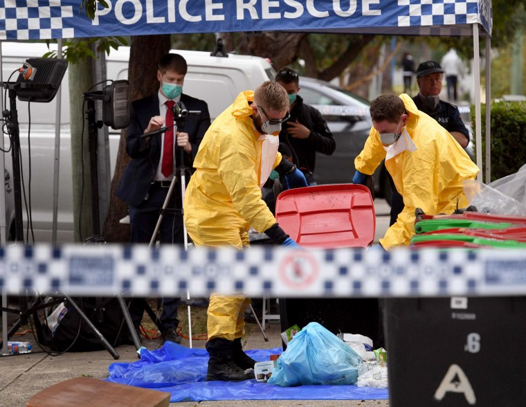 Image: Police search for evidence at a block of apartment