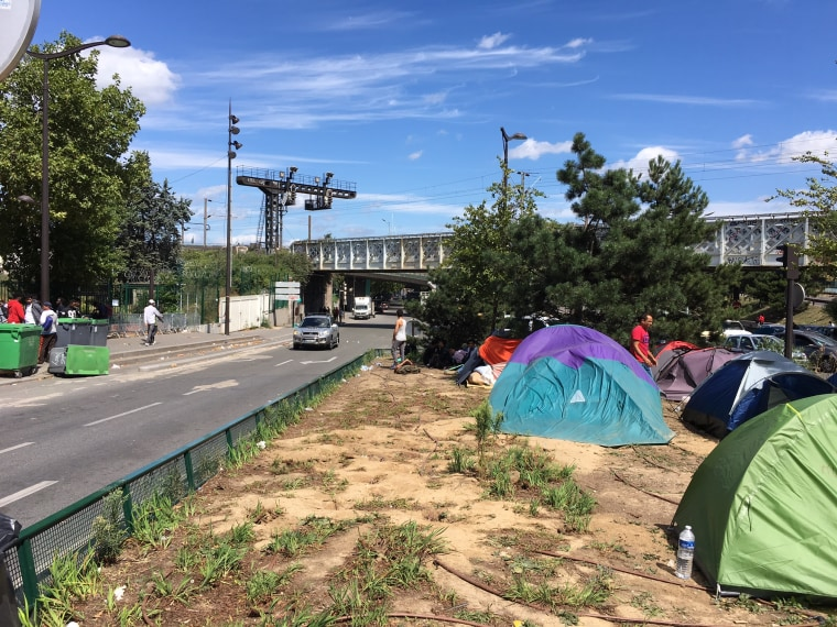 Image: Migrants living in the median between traffic lanes at Porte de la Chapelle, Paris.