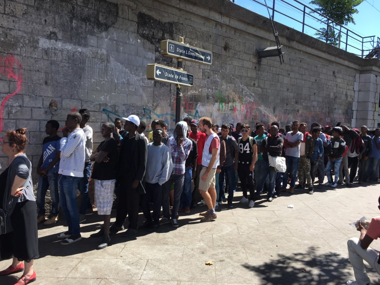Image: Migrants line up for breakfast distributed by volunteers in Porte de la Chapelle, Paris.