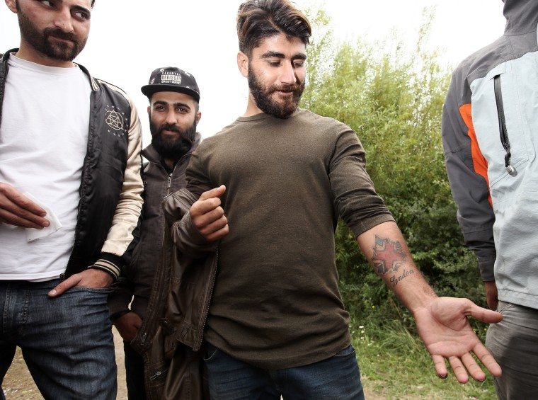 "Image: Kurdish migrant Ryan Salah Jabar shows off his ""London"" tattoo near Dunkirk, northern France."