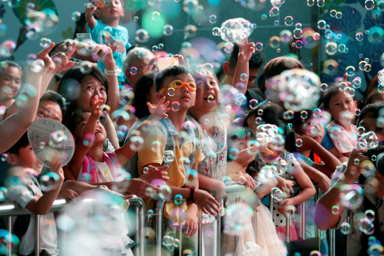 Image: People react in front of bubbles outside Harbour City mall in Hong Kong