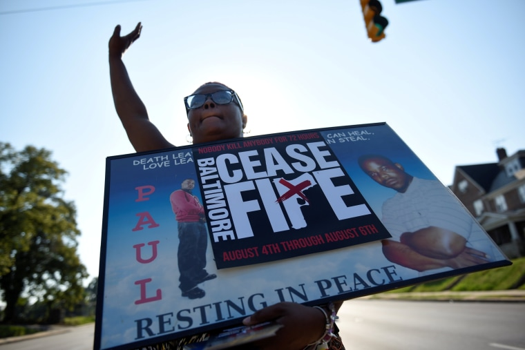 "Image: A relative of a gun violence victim holds a sign at the ""Stop the Violence"" rally in Baltimore"